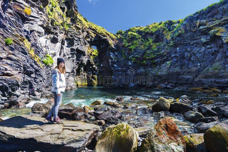 O adolescente da menina está ficando no primeiro plano de penhascos de Valasnos na costa do sul da península de Snaefellsnes em I imagem de stock