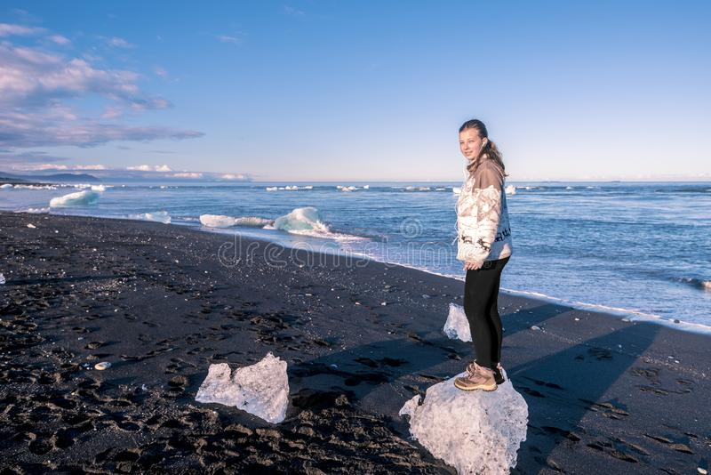 O adolescente da menina está ficando nos iceberg pequenos na beira de Oceano Atlântico, perto da lagoa da geleira de Jokulsarlon  imagens de stock royalty free