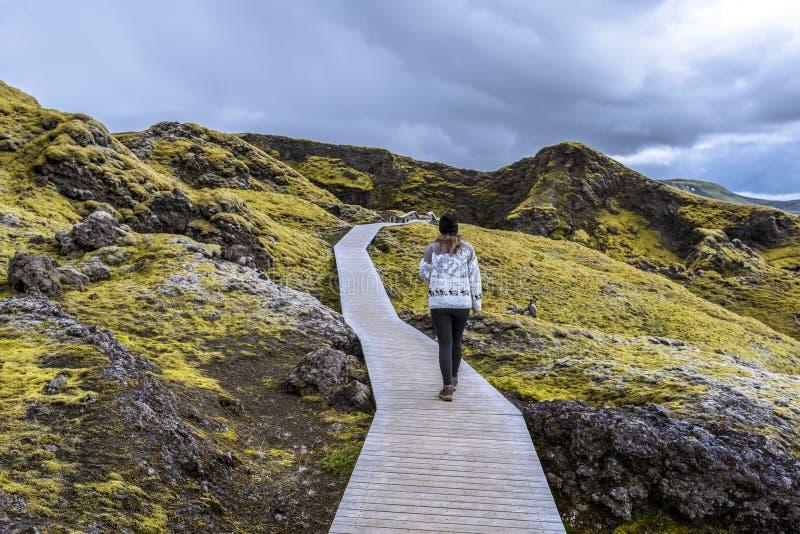 O adolescente da menina está seguindo a passagem de madeira do pé à cratera Tjarnargigur na área vulcânica da fissura de Lakagiga foto de stock