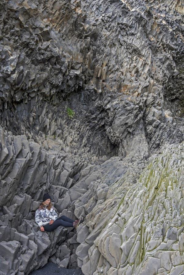 O adolescente da menina está sentando-se confortavelmente em penhascos do basalto no fundo da montanha de Reynisfjall Praia de Re foto de stock
