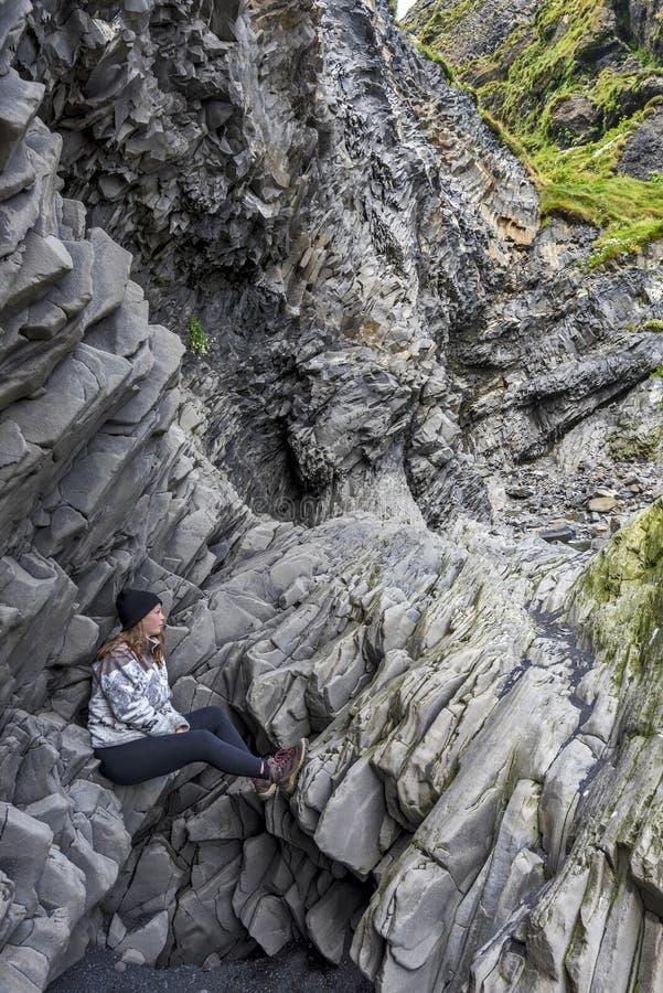 O adolescente da menina está sentando-se em penhascos do basalto no fundo da montanha de Reynisfjall Praia de Reynisfjara em Islâ fotografia de stock