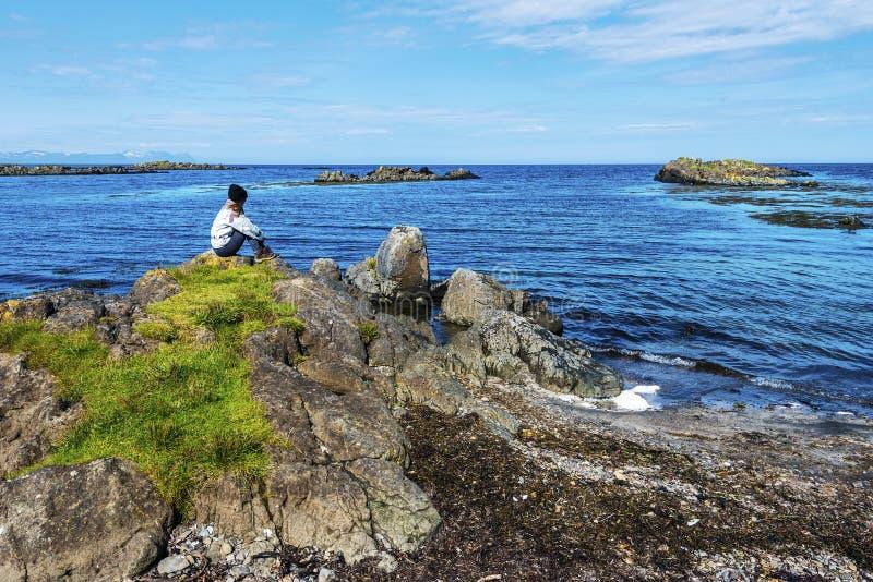 O adolescente da menina está situando na beira da baía de Hunar que olha a paisagem selvagem da costa ocidental da península de V imagens de stock royalty free