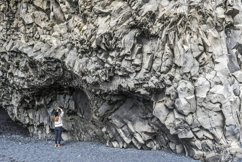 O adolescente da menina está tomando a imagem de penhascos do basalto no fundo da montanha de Reynisfjall em Islândia do sul fotografia de stock