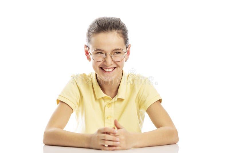 O adolescente da menina nos vidros senta-se na tabela e nos risos Isolado em um fundo branco imagens de stock