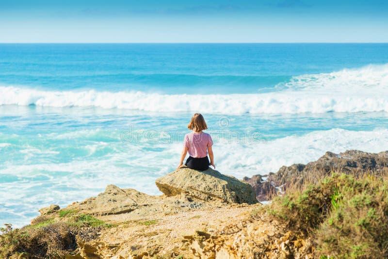 O adolescente da menina olha o mar das rochas fotografia de stock