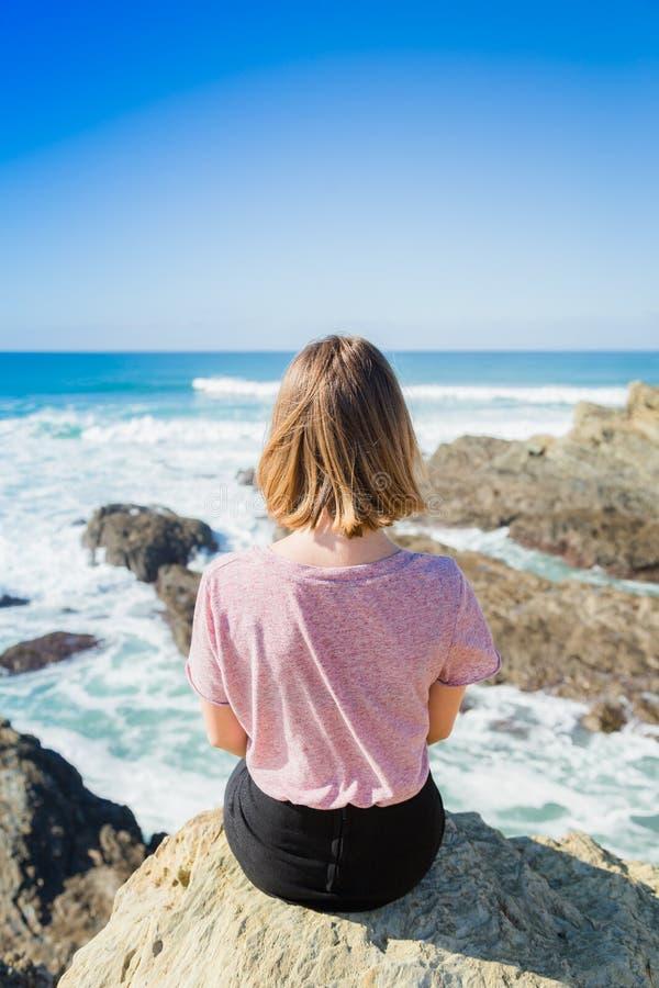 O adolescente da menina olha o mar das rochas fotos de stock royalty free