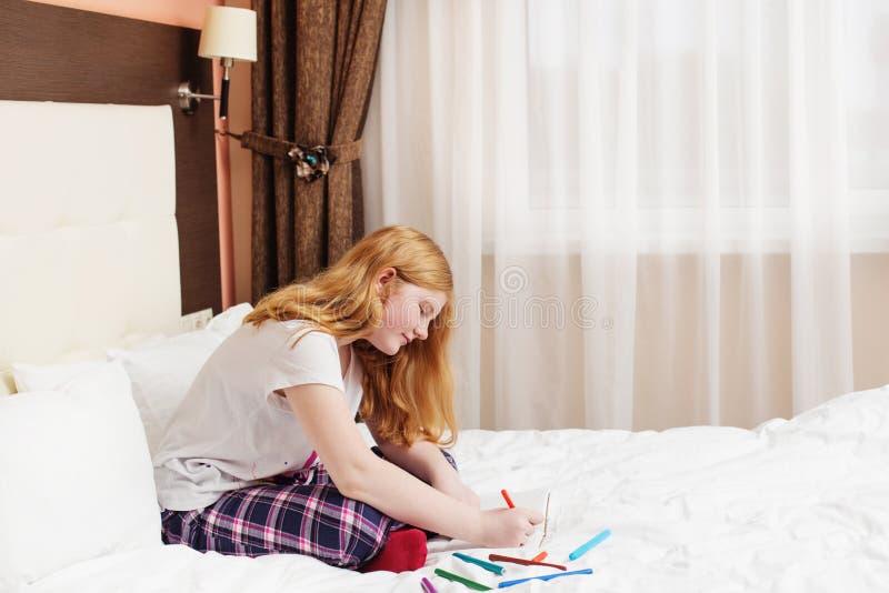 O adolescente da menina tira na cama fotografia de stock
