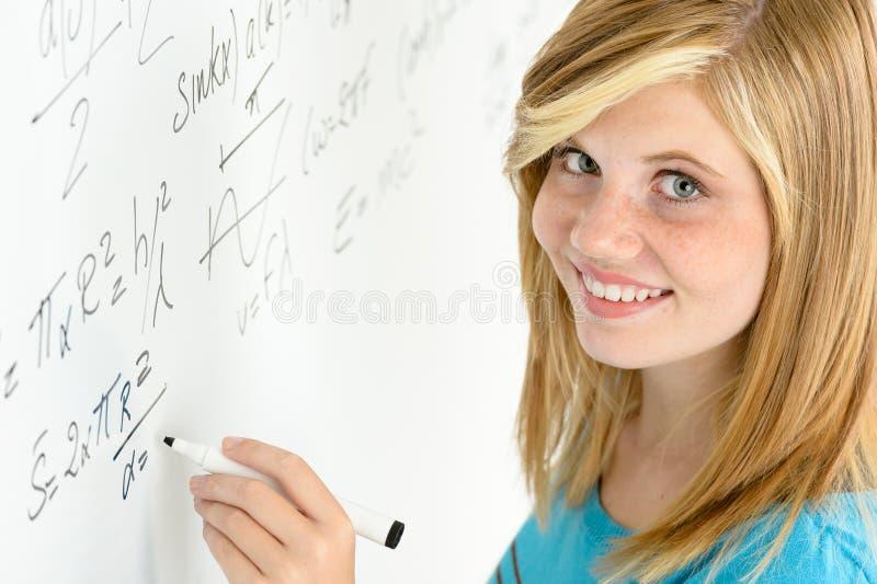 O adolescente do estudante escreve a matemática a placa branca foto de stock