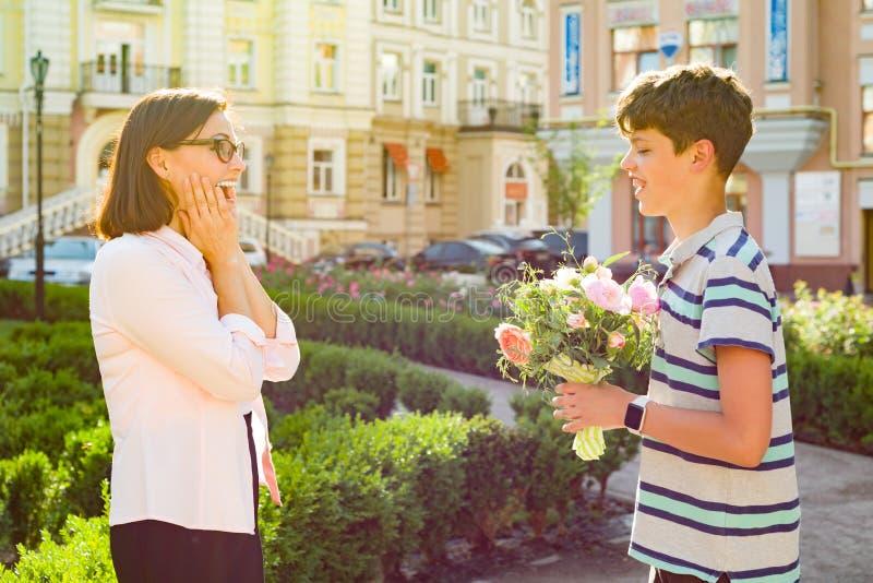 O adolescente do filho felicitou a mãe com um ramalhete da surpresa das flores foto de stock