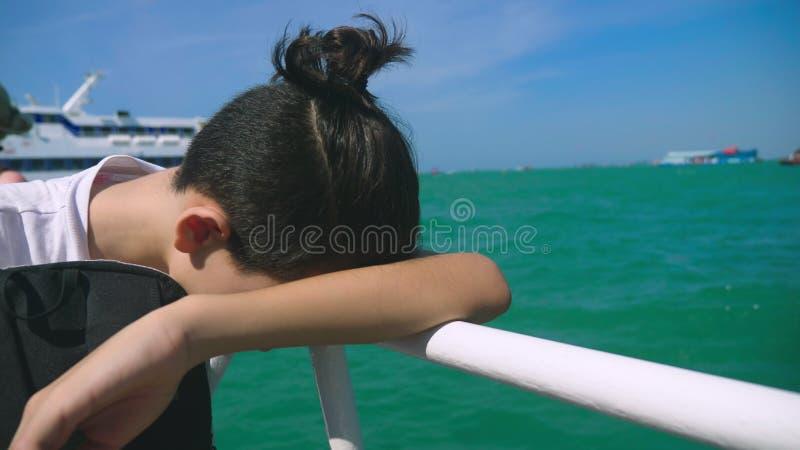 O adolescente do menino sofrer do enjoo quando em uma viagem do barco Medo da viagem ou doença do vírus durante a fotos de stock royalty free