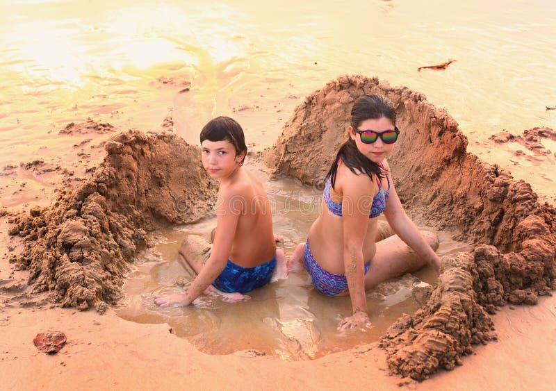 O adolescente e a menina jogam com a areia na praia imagens de stock royalty free