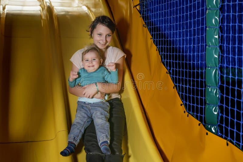 O adolescente e uma criança pequena estão rolando felizmente para baixo o monte fotografia de stock