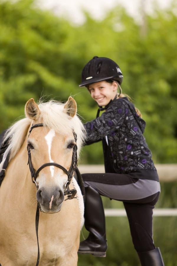 O adolescente escala o cavalo fotografia de stock