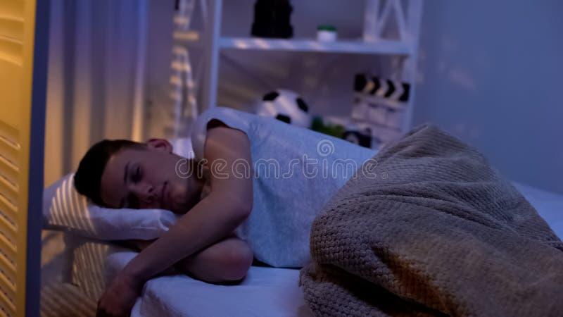 O adolescente esgotado que dorme na noite, estudante sobrecarregado precisa o resto, divisão fotografia de stock royalty free