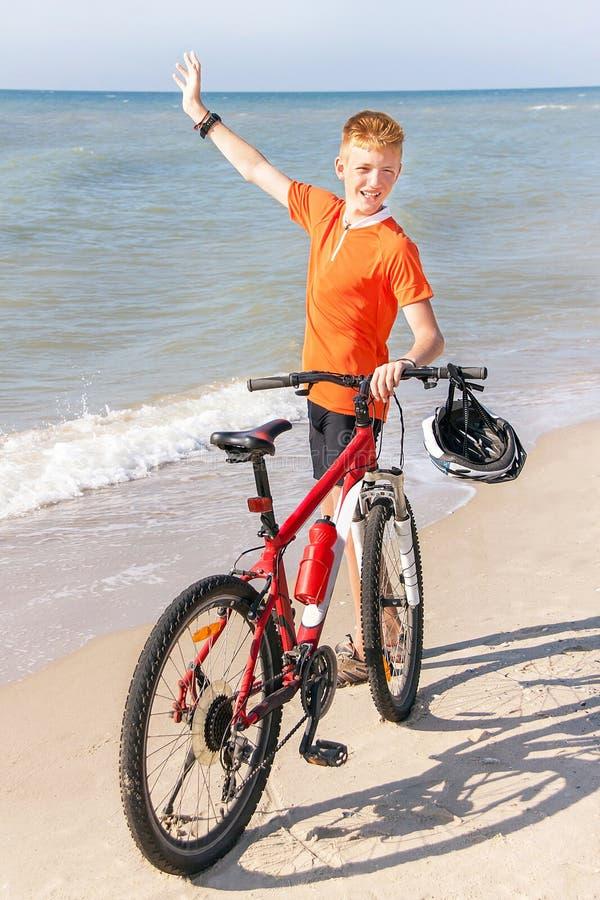 O adolescente está levantando com bicicleta em um fundo do mar fotos de stock royalty free