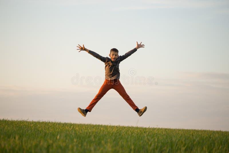 O adolescente está voando sobre o campo no por do sol fotos de stock