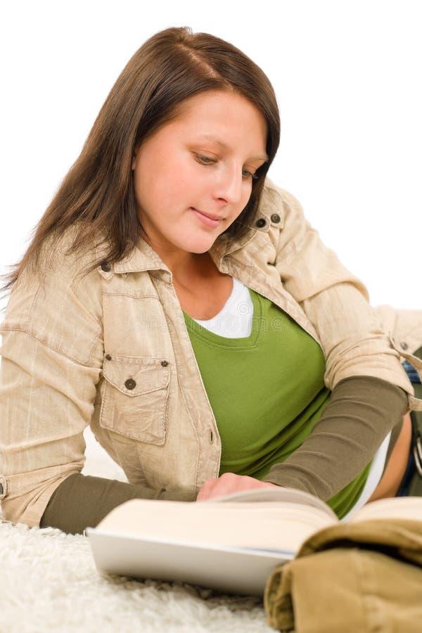O adolescente fêmea do estudante escreve trabalhos de casa com livro imagens de stock