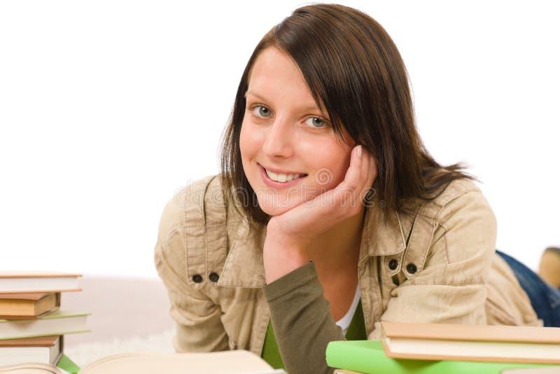 O adolescente fêmea do estudante escreve trabalhos de casa com livro fotos de stock royalty free