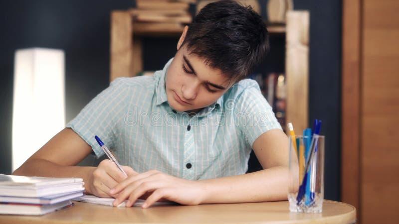O adolescente faz lições e escreve-as imagem de stock