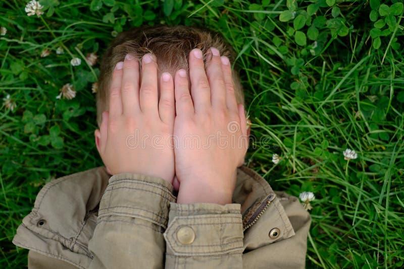 O adolescente fecha seus olhos com mãos fotos de stock