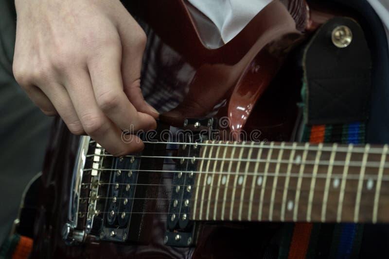 O adolescente joga a guitarra elétrica Os dedos de um baixista novo estão puxando cordas baixas Tema musical Close-up fotos de stock
