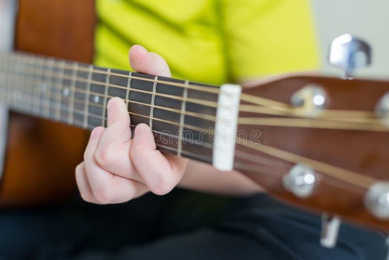 O adolescente joga uma guitarra acústica imagem de stock