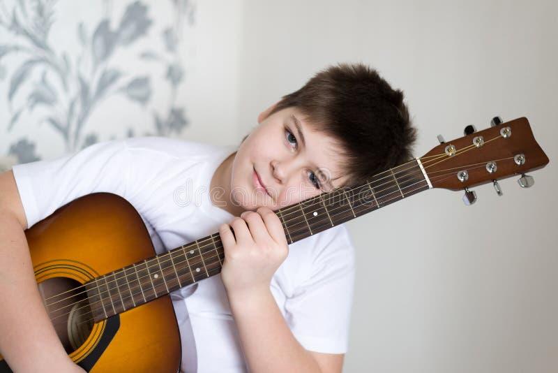 O adolescente joga uma guitarra acústica fotografia de stock