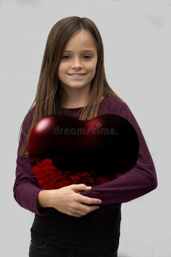 O adolescente leva um coração vermelho grande fotografia de stock