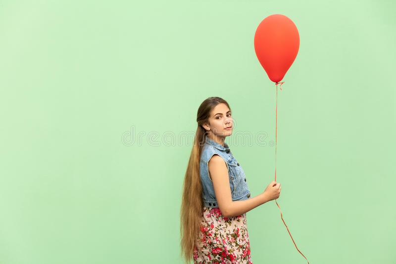 O adolescente louro bonito que olha a câmera, guardando o balão vermelho em um fundo verde fotos de stock