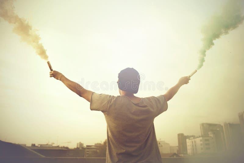 O adolescente masculino que guarda o fumo colorido cola acima no ar sobre o fundo urbano da cidade no por do sol fotos de stock