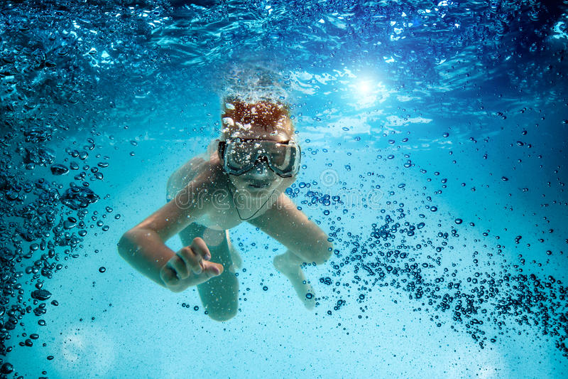 O adolescente na máscara e o tubo de respiração nadam debaixo d'água. imagens de stock royalty free