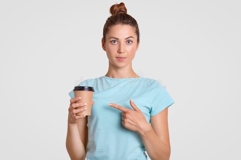 O adolescente novo bonito oferece-lhe o café ou o cappuccino do copo descartável, vestido no equipamento ocasional, isolado sobre imagens de stock