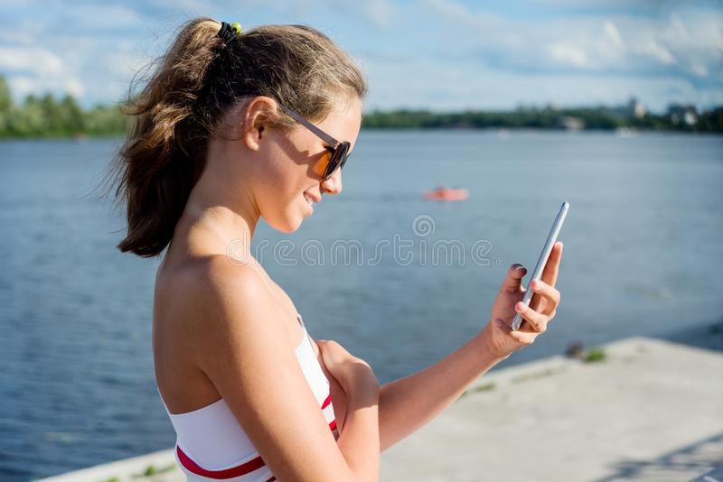 O adolescente novo dispara no vídeo em um smartphone para seu canal Em um dia de verão ensolarado, no parque da cidade imagens de stock