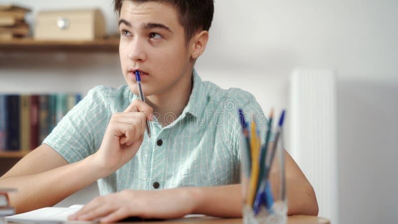 O adolescente pensa e faz as lições imagens de stock