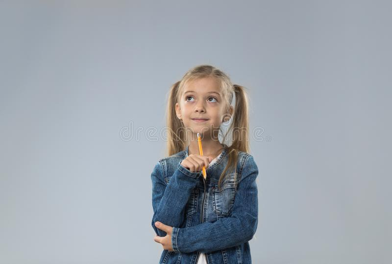 O adolescente pequeno no revestimento das calças de brim, criança pequena que olha acima para copiar o espaço pensa a posse Chin imagem de stock royalty free