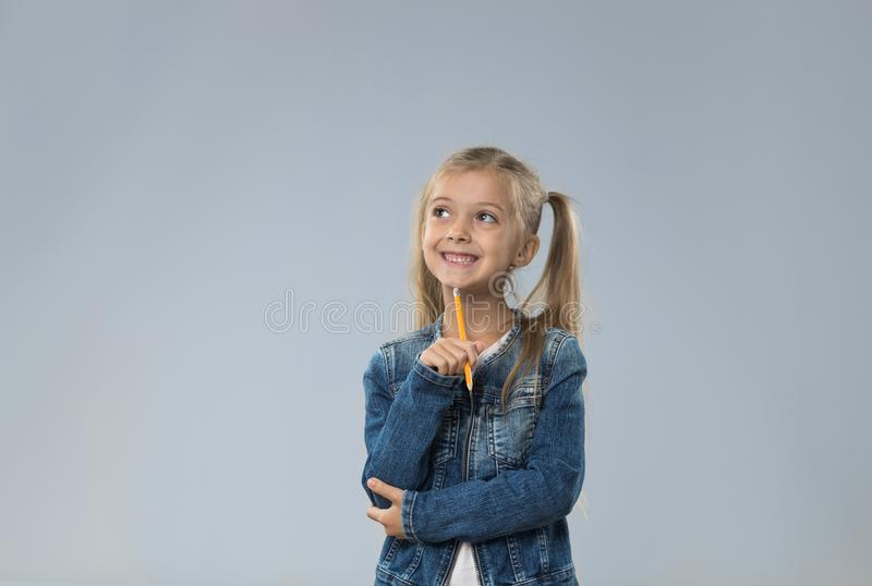 O adolescente pequeno no revestimento das calças de brim, criança pequena que olha acima para copiar o espaço pensa a posse Chin fotografia de stock