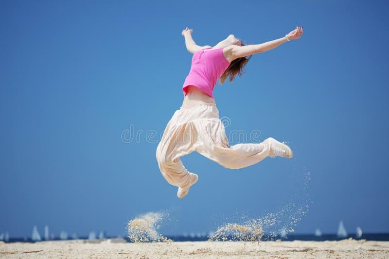 O adolescente que salta na praia fotografia de stock