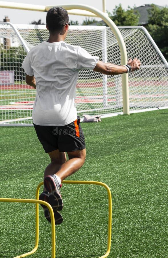 O adolescente que salta sobre mini obstáculos amarelos em um campo do relvado imagem de stock royalty free
