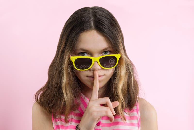 O adolescente sério 13,14 anos em vidros amarelos brilhantes mostra fora o sinal do silêncio, mantém o dedo dianteiro nos bordos, imagem de stock