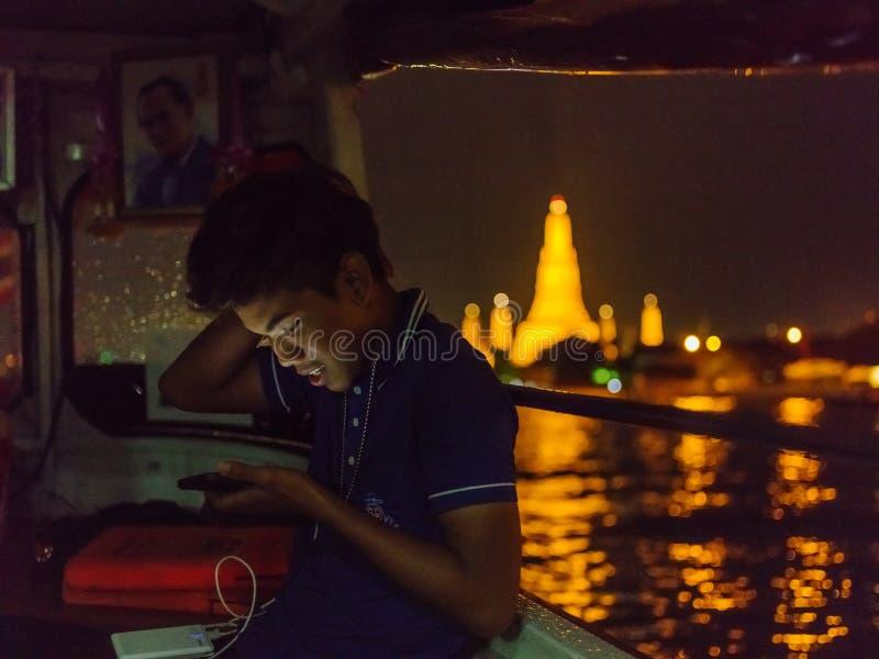 O adolescente tailandês navega pelo barco ao longo do rio de Chaopraya perto de Wat Arun foto de stock