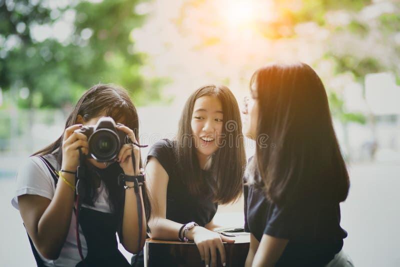 O adolescente três asiático com câmera do dslr levanta à disposição como o modelo de forma fotografia de stock