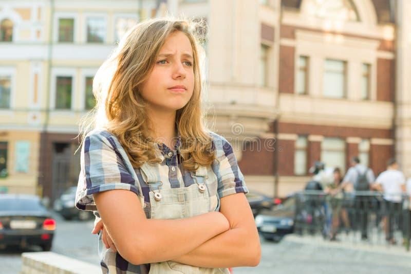 O adolescente triste da menina com braços cruzou-se em uma rua da cidade imagens de stock