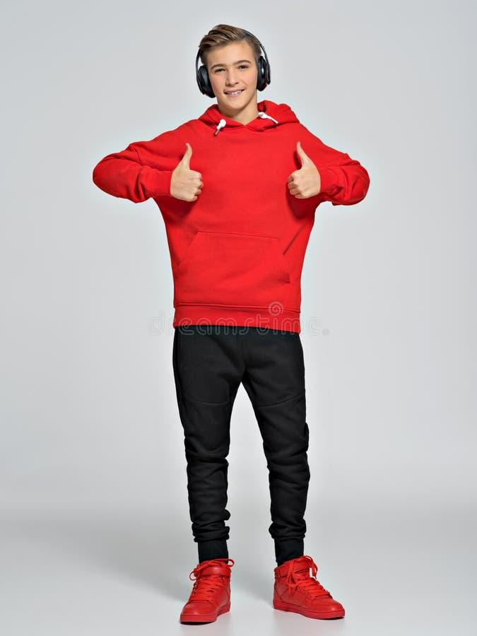 O adolescente vestiu-se em um hoodie vermelho e nas sapatilhas da rua imagens de stock royalty free