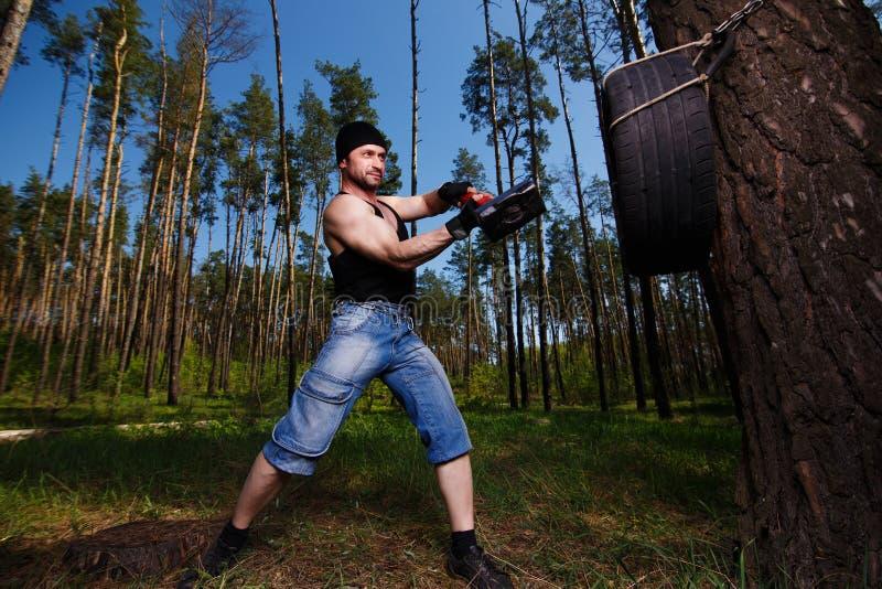 O adulto saudável forte rasgou o homem com os músculos grandes que batem o tyr do carro fotos de stock