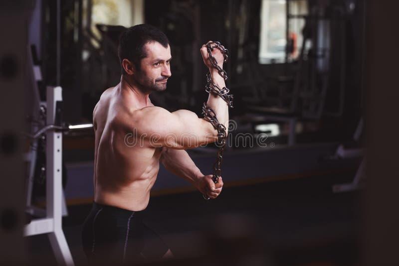 O adulto saudável forte rasgou o homem com os músculos grandes que levantam com cha fotografia de stock royalty free