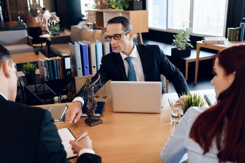 O advogado da família mostra a pares novos onde assinar o acordo no divórcio O par de divórcio dissolve o contrato de união fotos de stock