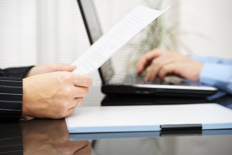 O advogado está lendo o contrato e o cliente do negócio está datilografando no regaço fotografia de stock royalty free
