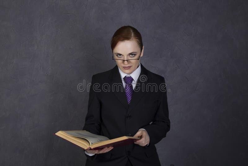 O advogado fêmea lê um livro grande com expressão séria, a mulher em um terno do ` s do homem, o laço e os vidros foto de stock