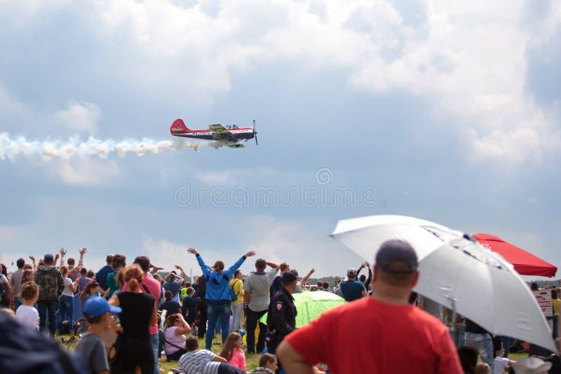 O aer?dromo de Mochishche, o festival a?reo local, os iaques 52 no c?u azul com fundo das nuvens e muitos visores, povos olham o  foto de stock