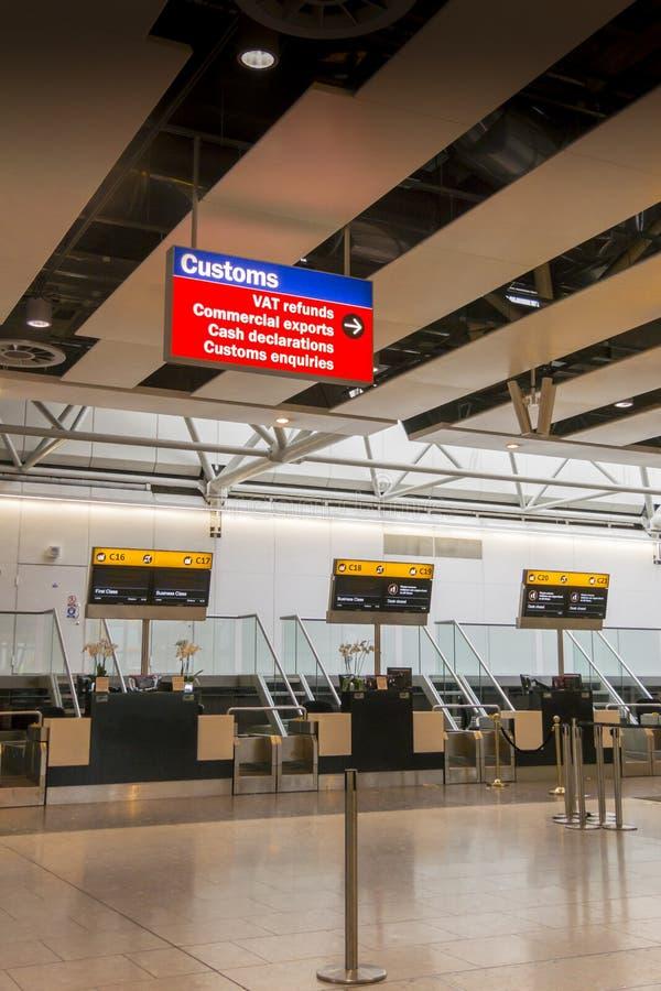 O aeroporto verifica dentro o sinal das mesas e da alfândega imagens de stock royalty free
